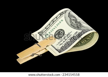 American dollars with with a wooden clothespin on black background - stock photo