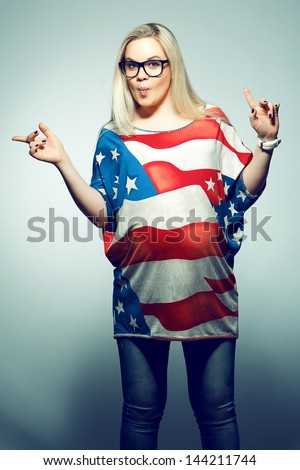 American Dream (Lifestyle) Concept: Young pregnant woman in american flag like dress and trendy glasses dancing over gray background with a fish face emotion (kiss). Hipster style. Studio shot