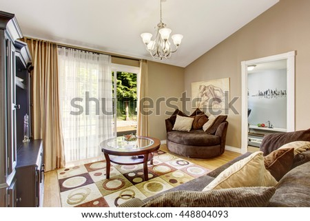 American family room with brown sofa set, rug, glass top coffee table and vaulted ceiling.