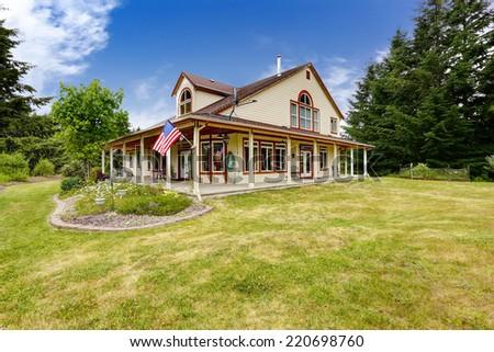 American farm house exterior with wraparound patio area - stock photo
