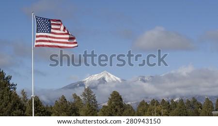 American Flag above Snow capped peaks.  San Francisco Peaks.  Flagstaff, Arizona. - stock photo