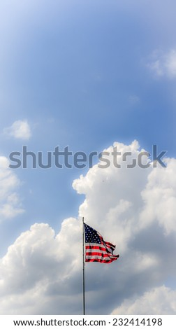 American Flag Against Blue Sky Cloudscape - stock photo