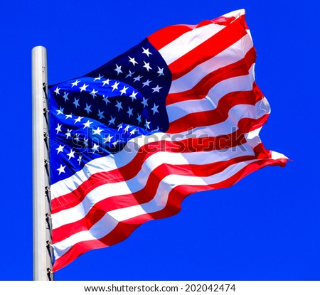 American flag against bright blue sky - stock photo