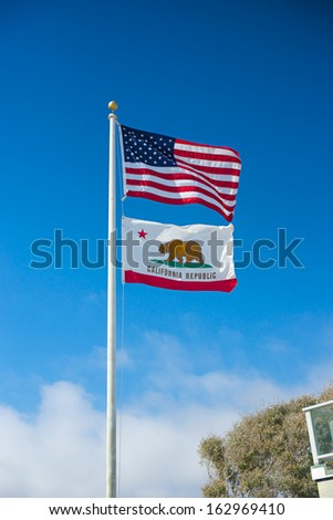 American flag and Californian flag wave in the breeze under a bright blue sky. - stock photo