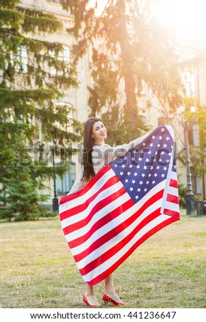 American flag and woman (4th july). Beautiful young woman with classic dress holding american flag in the park. fashion model holding us smiling and looking at camera. usa lifestyle.