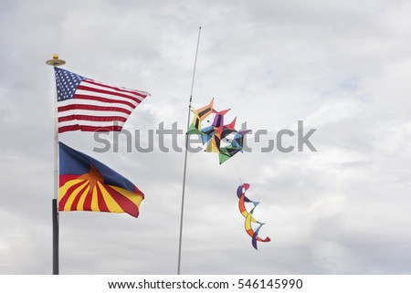 American Flag, Arizona Flag, Windsock against a cloudy sky