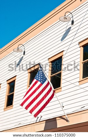 American flag attached to a small town building in the USA