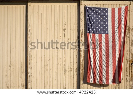 American flag displayed on the side of an old building - stock photo