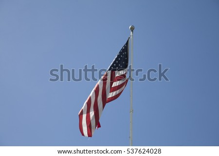 American flag flapping against a beautiful blue background