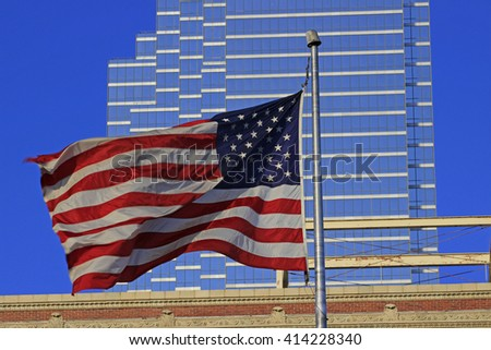American Flag fluttering in front of blue skyscraper - stock photo