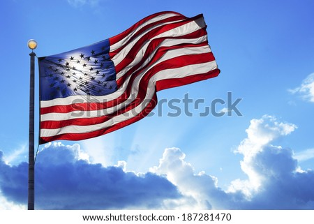 American flag fluttering in the wind under a cloudy sky - stock photo