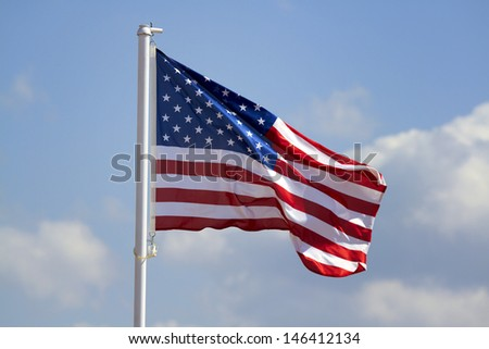 American flag flying, blue sky on the background