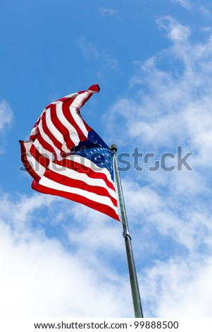 American flag flying in the breeze against a blue sky with white clouds - stock photo