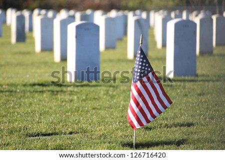 American flag in foreground of cemetery grave marker tombstones - stock photo