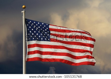 American flag in foreground, waving and brightly lit with ominous clouds in the background. / Old Glory Aglow / Brightly lit stars and stripes. - stock photo
