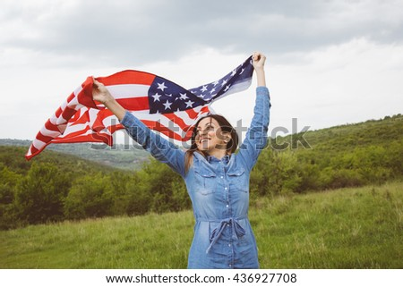 American flag in hands of jolly young woman.She is posing among lively green tree tops in vivid meadow on cloudy spring day.She is dressed in stylish denim dress.Patriotic concepts.