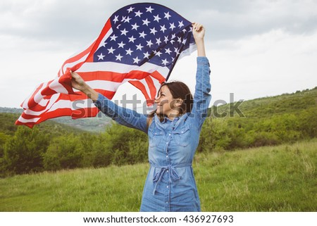 American flag in hands of vivacious happy young woman, posing  in bright green meadow,among hills,on cloudy day.