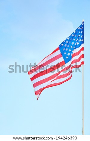 American flag on a post with cloudy background - stock photo