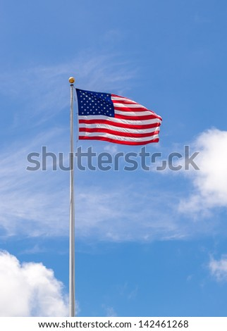 American Flag on Flagpole Waving in Blue Sky - stock photo