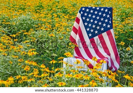 American flag on white wicker chair in field of yellow daisies - stock photo