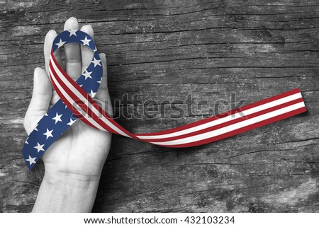 American flag pattern awareness ribbon color splashed on human hand grunge background: United states of america public holiday USA national day, nationalism raising US nation support campaign concept - stock photo