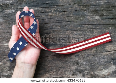 American flag pattern awareness ribbon on human hands on grunge aged wood background: United states of america public holiday - USA national day, nationalism raising US nation support campaign concept - stock photo
