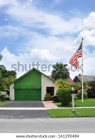 American Flag Pole Front yard Lawn suburban Back Split Style Home with Black top driveway Snout Garage Painted Green Residential Neighborhood USA Blue Sky Clouds Daytime - stock photo