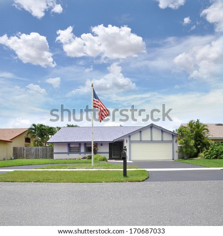 American Flag Pole Front yard lawn suburban ranch style gray and white home residential neighborhood USA blue sky clouds
