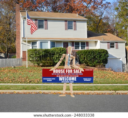 American flag pole Mannequin holding Real estate for sale open house welcome sign Suburban Tan High Ranch home with leaves on front lawn autumn day residential neighborhood Sunny blue sky