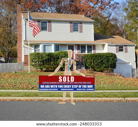 American flag pole mannequin holding Real estate sold (another success let us help you buy sell your next home) sign Suburban High Ranch home leaves on front lawn autumn day residential neighborhood