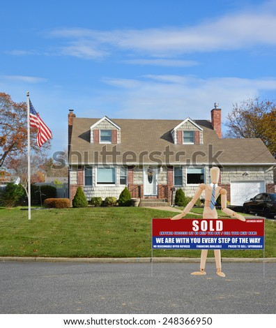 American flag pole Mannequin holding Real estate sold (another success let us help you buy sell your next home) sign Suburban Cape Cod home landscaped beautiful autumn day residential neighborhood USA - stock photo