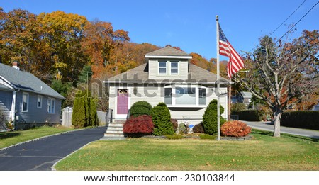 American Flag pole on front yard lawn of suburban bungalow style home residential neighborhood clear blue sky USA - stock photo