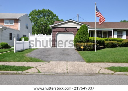 American flag pole on front yard lawn suburban home residential neighborhood USA clear blue sky