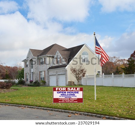 American flag pole Real Estate for sale open house welcome sign Suburban brick McMansion style home with two car garage white picket fence residential neighborhood blue sky clouds USA - stock photo