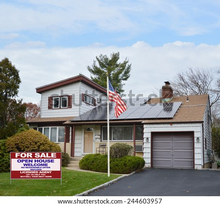 American flag pole real estate for sale open house welcome sign Suburban Ranch style home with solar panel on roof residential neighborhood USA blue sky clouds
