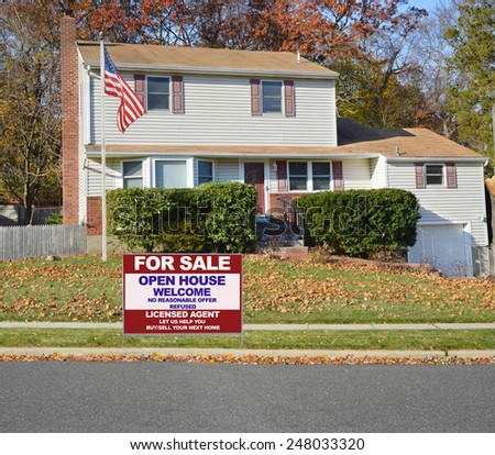 American flag pole Real estate for sale open house welcome sign Suburban Tan High Ranch home with leaves on front lawn autumn day residential neighborhood Sunny blue sky
