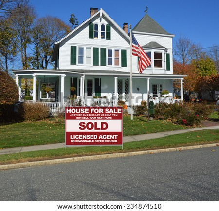 American flag pole Real Estate sold (another success let us help you buy sell your next home) side of suburban gable front Victorian style house in residential neighborhood clear blue sky USA - stock photo