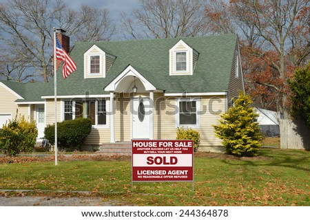 American flag pole Real Estate sold ( another success let us help you buy sell your next home) sign Suburban Cape Cod style home autumn day residential neighborhood USA - stock photo
