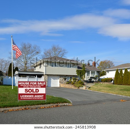 American flag pole Real estate sold (another success let us help you buy sell your next home) sign Suburban High Ranch Home with Siding and Stone sunny blue sky clouds residential neighborhood USA