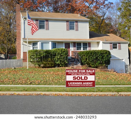 American flag pole Real estate sold (another success let us help you buy sell your next home) sign Suburban Tan High Ranch home with leaves on front lawn autumn day residential neighborhood blue sky