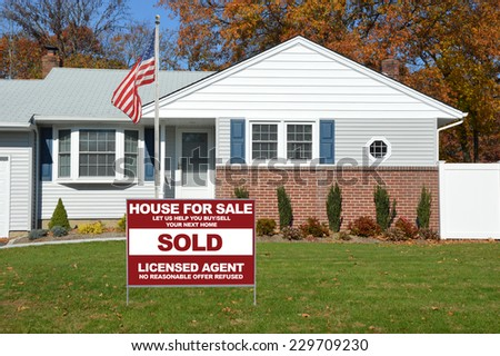 American Flag Pole Sold Real Estate (let us help you buy /sell your next home) suburban home residential neighborhood USA fall season blue sky - stock photo