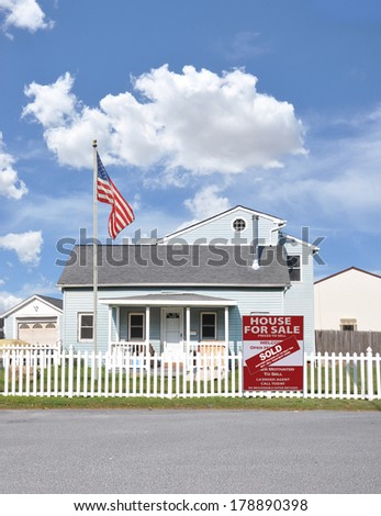 American Flag Pole Sold real estate sign (another success let us help you buy sell your next home) white picket fence Suburban Home Residential neighborhood USA Blue Sky Clouds - stock photo