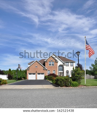 American Flag Pole Suburban Brick McMansion Home Two Car Garage Landscaped Yard Residential Neighborhood USA - stock photo