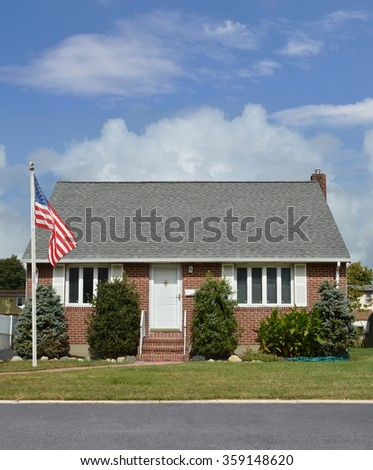 American flag pole Suburban Brownstone Brick Bungalow style home residential neighborhood blue sky clouds USA