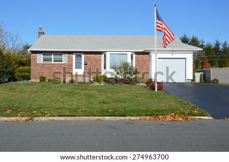 American flag pole Suburban brownstone brick ranch style home sunny clear blue sky residential neighborhood USA - stock photo