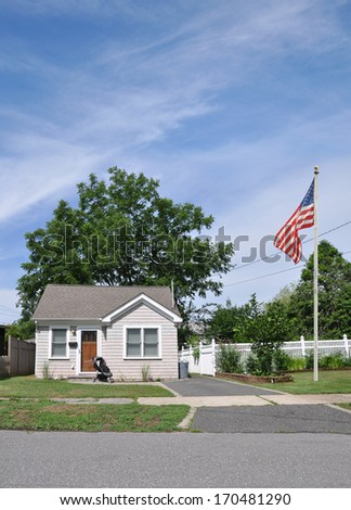 American Flag Pole Suburban Bungalow Home Baby Carriage Blacktop Driveway Sunny Residential Neighborhood Street USA Blue Sky Clouds - stock photo
