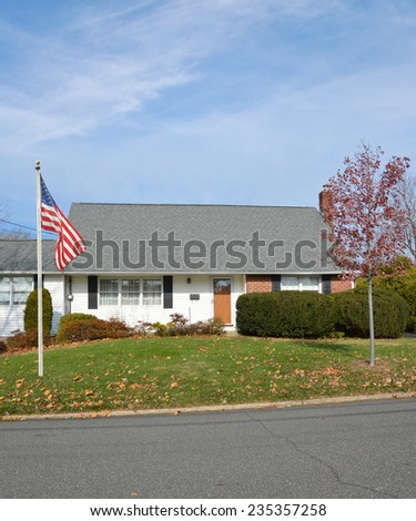 American flag pole suburban bungalow style home autumn season residential neighborhood blue sky clouds USA