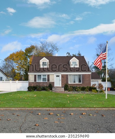 American flag pole suburban cape cod style home residential neighborhood autumn day blue sky clouds USA - stock photo