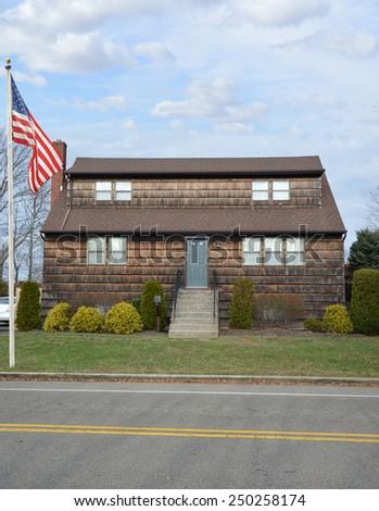 American flag pole Suburban Gable Front style home residential neighborhood USA - stock photo