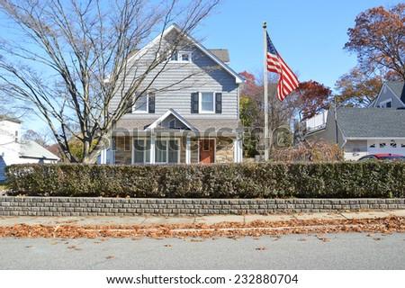 American flag pole suburban gable style house hedges autumn day residential neighborhood blue sky USA - stock photo